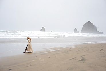 Woman talks on phone with Haystack Rock in the distance at popular tourist destination, Cannon Beach, Oregon, United States of America, North America