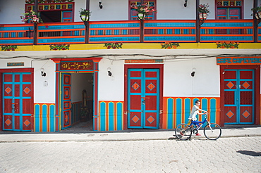 Boy walks his bike past colorful architecture next to Jardin's plaza, Jardin, Antioquia, Colombia, South America