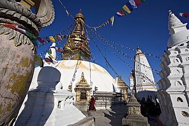 A monk walks clockwise around the buddhist stupa called Swayambhu or Swayambhunath, Kathmandu, Nepal
