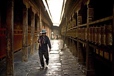 Man circuits the inner Jokhang temple, walking the circumambulation pathway (Nangkhor), Jokhang Temple, Barkhor, Lhasa, Tibet, China, Asia