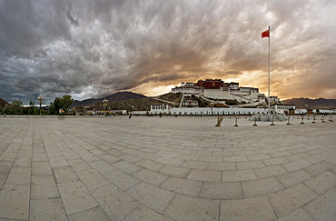 Panorama of dramatic evening sky over the Potala Palace, UNESCO World Heritage Site, and the red flag of China flutters over the Dalai Lama's former home, Lhasa, Tibet, China, Asia