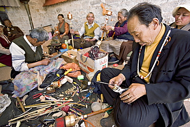 Carrying out routine maintenance of prayer wheels on a monastery roof, Lhasa, Tibet, China, Asia
