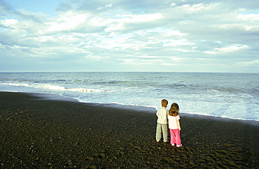 Two young children, boy and girl, on the beach at Napier, North Island, New Zealand, Pacific
