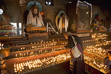 Old woman lighting butter lamps in front of Buddha statues draped with new silk scarves, in a small temple, at the Boudha or Bodhnath stupa, Tibetan New Year (Lhosar), Kathmandu, Nepal, Asia