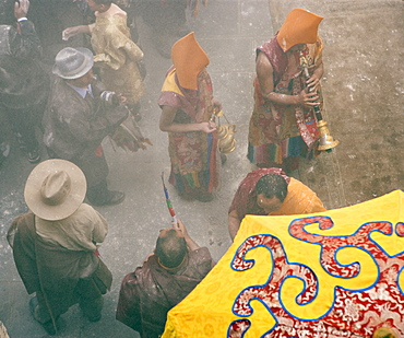 Yellow hat monks at Tibetan Buddhist new year (Lhosar), when flour thrown in the air as part of the celebrations, Samtenling monastery, Bodhnath, Kathmandu, Nepal, Asia