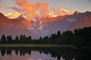 Sunset, Lake Matheson, with Mount Tasman and Mount Cook behind clouds, Westland Tai Poutini National Park, UNESCO World Heritage Site, West Coast, Southern Alps, South Island, New Zealand, Pacific