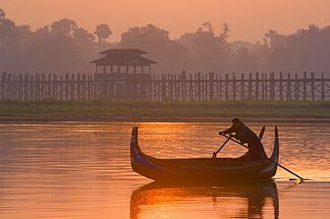Boat on Thaungthaman Lake, and U Bein's Bridge, at 1.2 km long the world's longest teak bridge, Amarapura, Myanmar (Burma), Asia
