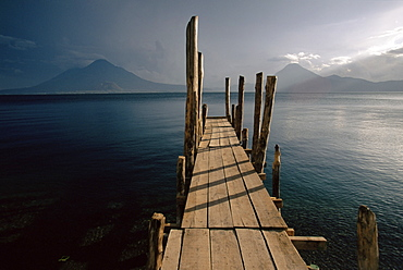 Wooden jetty and volcanoes in the distance, Lago Atitlan (Lake Atitlan), Guatemala, Central America