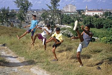 Four boys practicing kick boxing, martial arts moves in the El Cerro area of Havana, Cuba