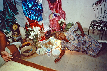 A woman lying down in front of the Santeria altar in her home in the Los Pinos area of Havana, Cuba