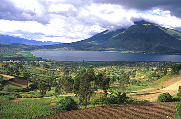 Imbabura Volcano, 4609, meters high, above the waters of Laguna San Pablo with the fields around the town of Otavalo in the foreground, North of Quito, Highlands, Ecuador