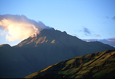 At sunset, clouds hang from the crater of Imbabura Volcano, 4609 meters high, above Laguna San Pablo and the town of Otavalo, North of Quito, Highlands, Ecuador