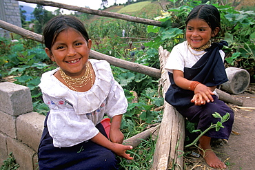 Young sisters in traditional Otavalo dress on their family's farm above Laguna San Pablo and the town of Otavalo, North of Quito, Highlands, Ecuador