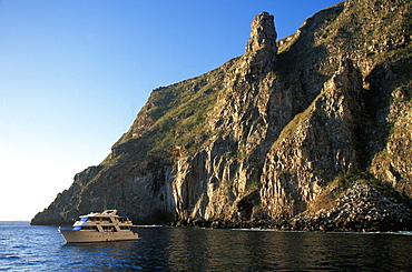Steep, rugged, volcanic cliffs surround Wolf Island one of the newest and most northerly of the Galapagos with scuba diving boat, Galapagos Islands, Ecuador