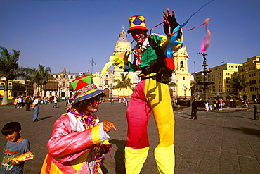 Street entertainers on stilts perform in the Plaza de Armas with the Cathedral, built in 1564-1625, (rebuilt in the 18thc) beyond, Colonial Architecture, Lima, Peru