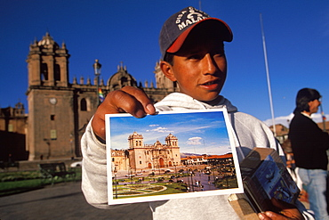 Ancient capital of the Incas the Plaza de Armas with a young boy selling postcards of the Cathedral with the Cathedral beyond, Cuzco, Highlands, Peru