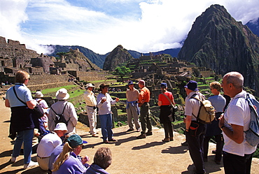 Machu Picchu tourist group with guide visiting the ancient city enormous numbers of tourists come to the site each year, Highlands, Peru