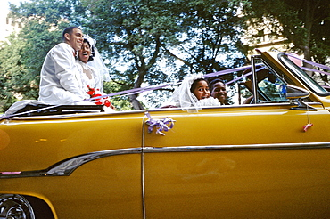 Just married bride and groom after wedding ceremony riding in back seat of vintage American car in Centro Habana, Havana, Cuba