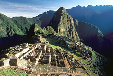 Machu Picchu view of the ancient city with Huayna Picchu Peak above the Rio Urubamba terraces, city walls and gate in foreground, Highlands, Peru