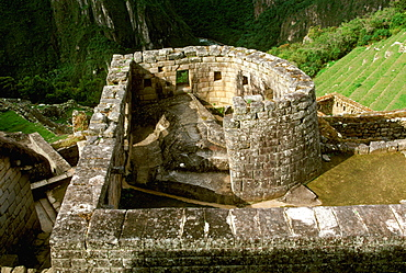 Machu Picchu the Temple of the Sun with the site's most perfect stonework encloses a rock below aligned window to indicate the solstice, Highlands, Peru
