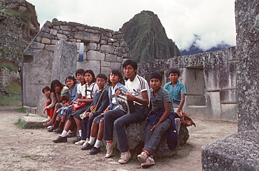 Machu Picchu The Temple of the Three Windows in the Sacred Area, and group of visiting Peruvian school children, Highlands, Peru
