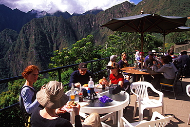 Machu Picchu hikers eating hamburgers in the outdoor cafe after having completed the trek of the Inca Trail, Highlands, Peru