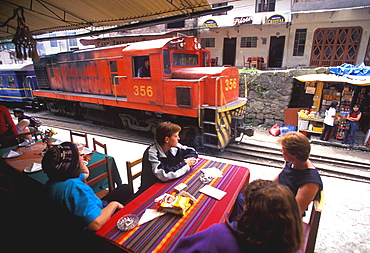 Machu Picchu the train from Cuzco arrives in Aguas Calientes the town and station below site train passes restaurants on main street, Highlands, Peru