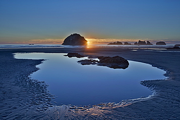 Sunset by a sea stack over a pool on the beach, Bandon Beach, Oregon, United States of America, North America