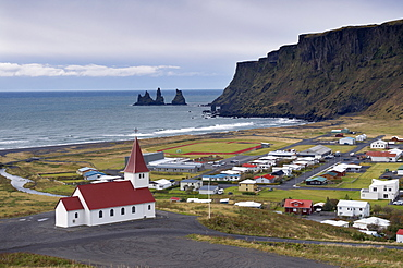 Church, village of Vik (Vik a Myrdal) and Reynisdrangar sea stacks in the distance, Iceland, Polar Regions