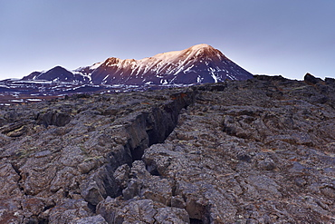 Deep crack in lava field near Lake Myvatn, Mount Hlidarfjall, 771m, in the distance, northern Iceland, Iceland, Polar Regions