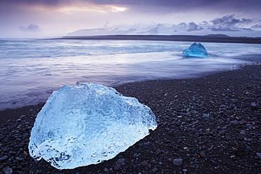 Iceberg washed ashore on Breidamerkursandur black sands, near Jokulsarlon glacial lagoon, East Iceland, Polar Regions