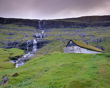 Traditional turf roofed farm building and waterfall, Saksun, Streymoy Island, Faroe Islands (Faroes), Denmark, Europe