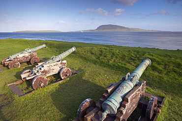Skansin fort, old fort guarding Torshavn and its harbour, with old brass cannons, Second World War British marine guns and lighthouse, Nolsoy in the distance, Torshavn, Streymoy, Faroe Islands (Faroes), Denmark, Europe