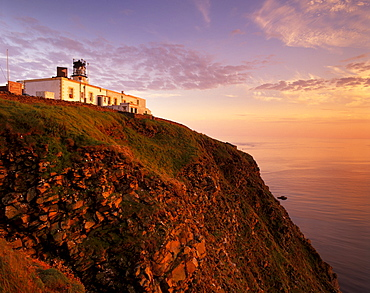 Sunset over Sumburgh Head lighthouse, built by Robert Stevenson in 1821 and now an RSPB office, Shetland Islands, Scotland, United Kingdom, Europe