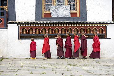 Buddhist monks turning prayer wheels, Karchu Dratsang Monastery, Jankar, Bumthang, Bhutan, Asia