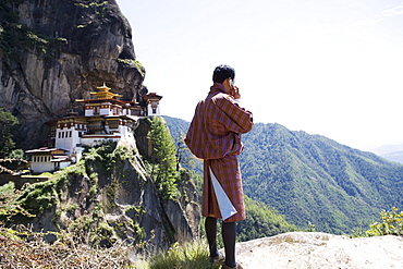 Bhutanese man with cell phone, Taktshang Goemba (Tiger's Nest) Monastery, Paro, Bhutan, Asia