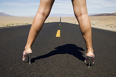 Woman in high heels on empty road, Death Valley National Park, California, United States of America, North America