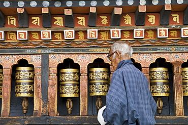 Old Bhutanese man turning prayer wheels in Buddhist temple, Thimphu, Bhutan, Asia