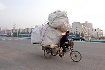 Transporting a precarious load through Beijing, China, Asia