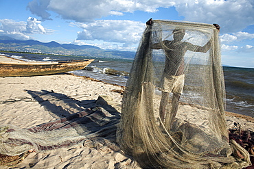 A fisherman tends his nets on Plage des Cocotiers (Coconut Beach) also known as Saga Beach, Lake Tanganyika, Bujumbura, Burundi, East Africa, Africa