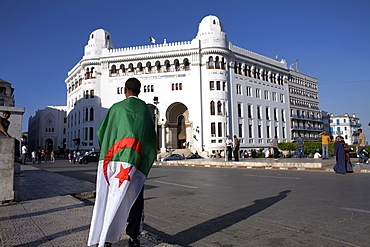 A man with an Algerian flag stands in front of Grande Poste in Algiers, Algeria, North Africa, Africa