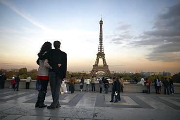 A couple look towards the Eiffel Tower, Paris, France, Europe