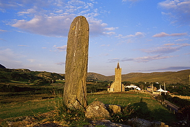 Standing stone and church, village of Glencolumbkille, County Donegal, Ulster, Republic of Ireland, Europe