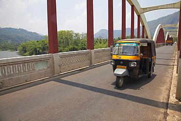 Tuk tuk crossing the Neriamangalam Bridge in Munnar, Kerala, India, Asia