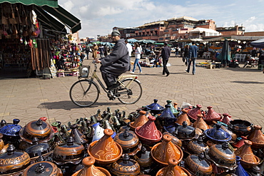 Cyclist passing a stall selling traditional clay tajine cooking pots in Place Jemaa el-Fna, Marrakesh, Morocco, North Africa, Africa