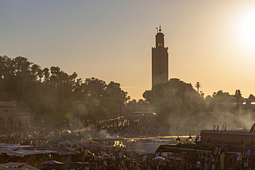 Evening light on the busy square of Place Jemaa el-Fna with the minaret of the Koutoubia Mosque in the distance, UNESCO World Heritage Site, Marrakech, Morocco, North Africa, Africa
