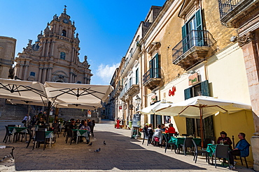 People dining in Piazza Duomo in front of Cathedral of San Giorgio in the historic hill town of Ragusa Ibla, Ragusa, UNESCO World Heritage Site, Sicily, Italy, Euruope