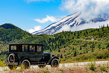 Beautifully restored Vintage American car passing Mount St. Helens, part of the Cascade Range, Pacific Northwest region, Washington States, United States of America, North America