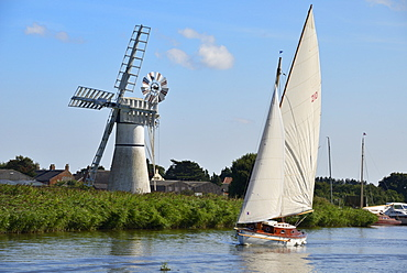 Sailing boat in front of Thurne Dyke Drainage Mill, windmill, Thurne, Norfolk, England, United Kingdom, Europe