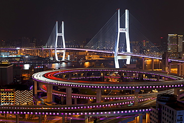 High angle wide shot traffic on Nanpu Bridge spiral and Bridge, illuminated at night, Shanghai, China, Asia